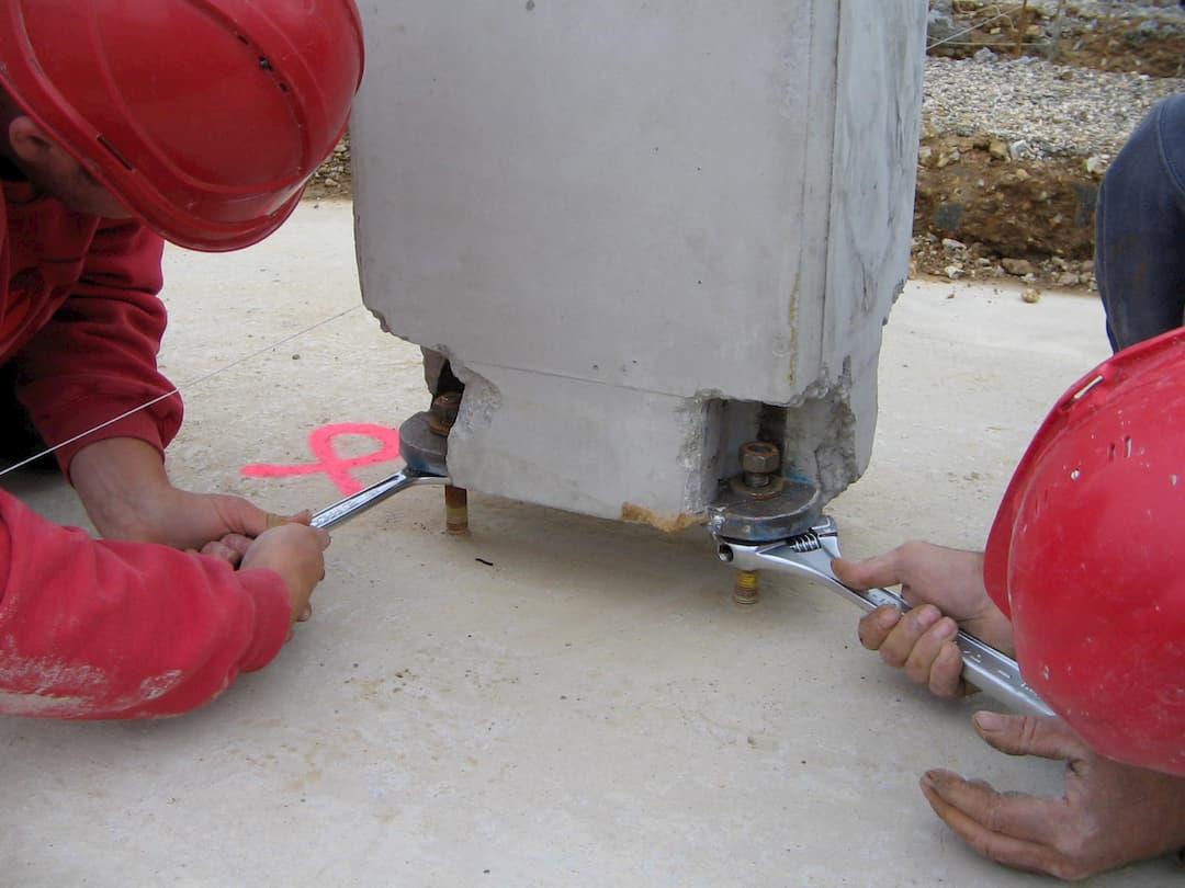 Boulonnage des poteaux béton aux pieds de poteau béton armé préfabriqué